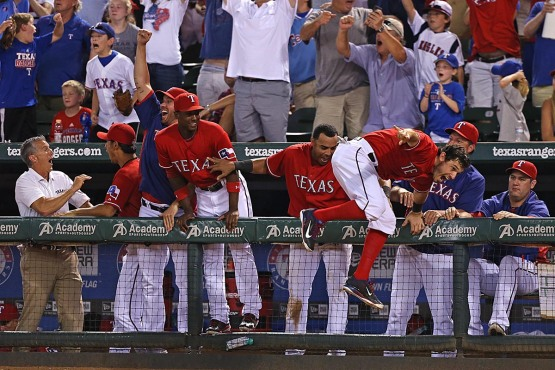 The Rangers watch the flight of Soto's ball in anticipation