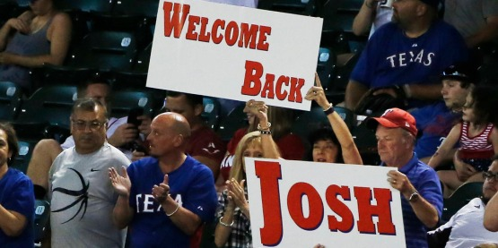 Texas Rangers fans show their support for outfielder Josh Hamilton during the ninth inning of a baseball game against the Boston Red Sox, Thursday, May 28, 2015, in Arlington, Texas. Hamilton played his first home game with Texas after being reacquired from the Los Angeles Angels. Boston won 5-1. (AP Photo/Brandon Wade)